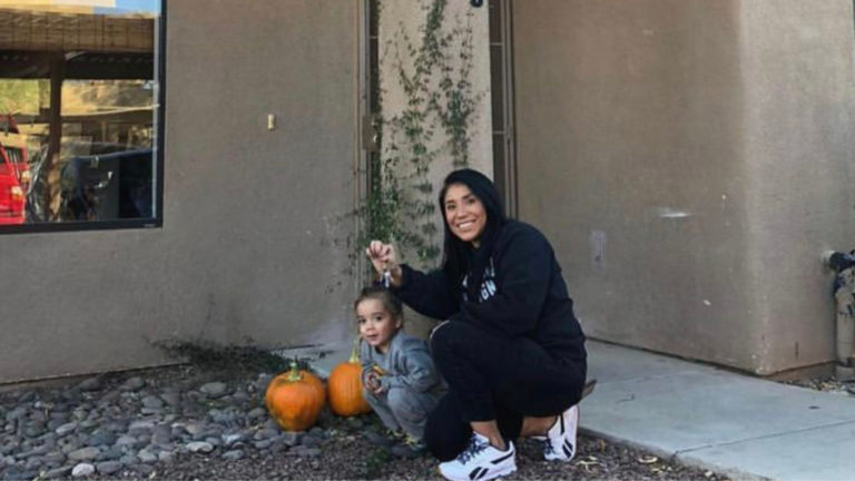 single mom with child smiling with keys to new house